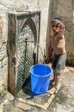 积水的男孩从喷泉在入口到菲斯麦地那在摩洛哥 免版税库存照片