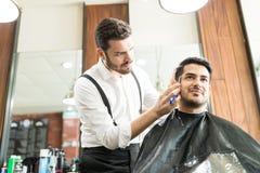 称呼客户` s胡子的确信的男性理发师在商店 免版税图库摄影