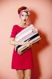 称呼有购物配件箱的红头发人女孩在桃红色背景。 库存照片