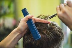 称呼他的客户的头发的专业理发师 库存照片