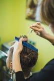 称呼他的客户的头发的专业理发师 免版税库存图片