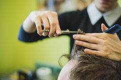 称呼他的客户的头发的专业理发师 免版税库存照片