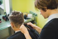 称呼他的客户的头发的专业理发师 免版税图库摄影
