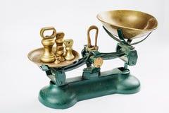称并且测量与老黄铜盘子的刻度尺 免版税库存图片
