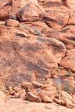 称红色岩石墙壁的爬山者在沙漠 免版税库存照片