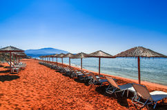 秸杆伞和sunbeds在一红色沙子海滩和绿松石wa 免版税库存照片