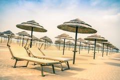 秸杆伞和sunbeds在里米尼在意大利靠岸 免版税库存图片