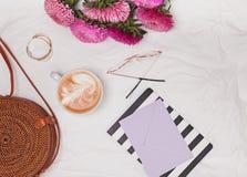 秸杆圈子袋子、咖啡、花和其他逗人喜爱的女性acessories在白色纺织品背景 免版税图库摄影