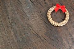 秸杆在木纹理的圣诞节花圈。 库存图片