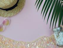 秸杆夏天帽子、金黄装饰网、心脏形状太阳镜、壳和棕榈叶 免版税库存照片