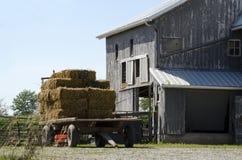 秸杆无盖货车和老谷仓 免版税库存照片