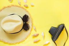 秸杆海滩foman ` s帽子,与减速火箭的照相机的黑太阳镜在黄色背景 顶视图 平的位置 文本的空间 旅行骗局 免版税库存照片
