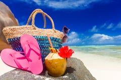 秸杆袋子、桃红色触发器、太阳镜和椰子在热带塞舌尔群岛靠岸 拉迪格岛海岛 免版税库存图片
