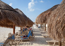 秸杆遮阳伞和在海滩的晒日光浴的椅子 免版税库存照片