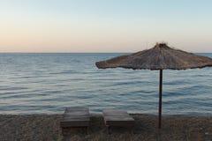 秸杆遮阳伞和sunbed在Pebble海滩 免版税图库摄影