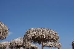 秸杆遮阳伞 使休息的季节、时期和旅行靠岸 安置文本 1个背景覆盖多云天空 从太阳的秸杆伞 免版税图库摄影