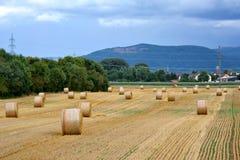 秸杆领域全景视图与圆的干燥干草捆的在山脉前面 库存图片