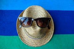 秸杆sunhat和太阳镜在海滩毛巾 免版税图库摄影