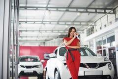 移交您新的汽车钥匙、经销权和销售概念的微笑的汽车推销员 愉快的女孩买家 免版税图库摄影