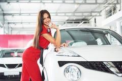 移交您新的汽车钥匙、经销权和销售概念的微笑的汽车推销员 愉快的女孩买家 免版税库存图片