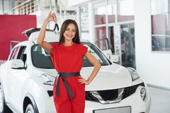 移交您新的汽车钥匙、经销权和销售概念的微笑的汽车推销员 愉快的女孩买家 库存图片