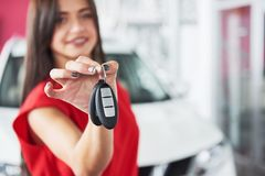 移交您新的汽车钥匙、经销权和销售概念的微笑的汽车推销员 愉快的女孩买家 免版税库存照片