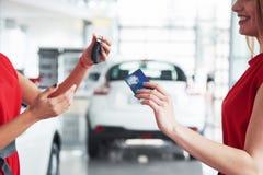 移交您新的汽车钥匙、经销权和销售概念的微笑的汽车推销员 愉快的女孩买家 图库摄影