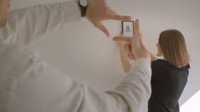 移动一栋新的舒适公寓的年轻快乐的夫妇特写镜头画象  女性拿着图片和决定它 股票视频