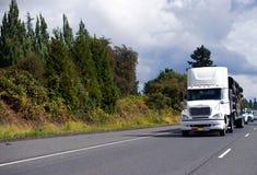 移动与在绿色宽高速公路机智的拖车的大半船具卡车 免版税库存图片