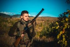 移动与猎枪的猎人寻找牺牲者 在伪装的猎人给准备好寻找穿衣与狩猎步枪 免版税图库摄影