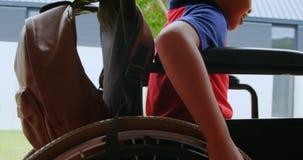移动他的在学校走廊4k的残疾非裔美国人的男小学生侧视图轮椅 影视素材