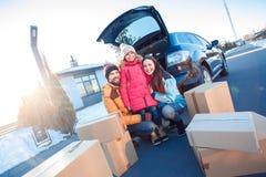 移动向新的公寓 户外一起坐在汽车附近的家庭围拢通过箱子微笑愉快 免版税库存图片