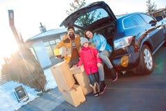 移动向新的公寓 户外一起站立坐的家庭在有箱子微笑的汽车愉快 库存图片