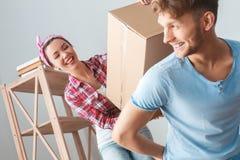 移动向新的地方女孩帮助的人的年轻夫妇运载看彼此的箱子愉快的特写镜头 免版税库存照片