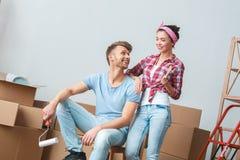 移动向新的安置人的年轻夫妇坐拿着漆滚筒的箱子看syanding与刷子笑的妇女 库存图片