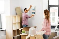 移动向新的家和垂悬的照片的愉快的夫妇 图库摄影