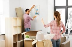 移动向新的家和垂悬的照片的愉快的夫妇 免版税库存照片