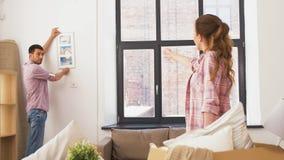 移动向新的家和垂悬的照片的愉快的夫妇 股票录像