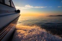 移动向日落的白色汽艇 免版税库存图片