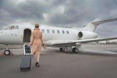 移动向有行李的飞机的女孩 免版税库存图片