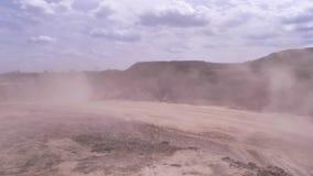 移动在与飞行尘土场面的沙子猎物的大,红色挖掘机 在露天开采的猎物的重的装载的倾销者卡车 影视素材