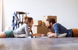 移动在新房里的年轻夫妇,说谎在地板上 图库摄影