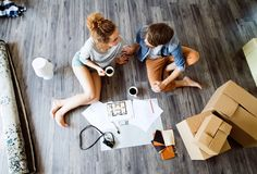 移动在新房,饮用的咖啡里的年轻夫妇 库存照片