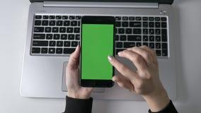 移动在智能手机` s触摸屏幕的女性手 绿色屏幕, chromakey概念,膝上型计算机在背景中 顶层 股票录像