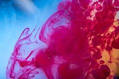 移动在水中的红色油漆漩涡喜欢在蓝色背景的烟 抽象背景 免版税库存图片