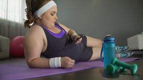 移动她的电话的懒惰肥胖女孩而不是减重的体育锻炼 影视素材