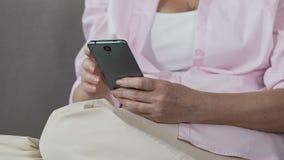 移动它的屏幕,容易的流动应用的退休的女性举行的智能手机 股票视频