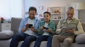 移动小配件,青春期前的男孩的成年男性打电子游戏,小配件瘾 影视素材