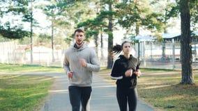 移动式摄影车一起跑在公园的被射击男性和女生在穿现代运动服的秋天天 常青杉木 影视素材