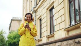 移动式摄影车听到与耳机的音乐,唱和使用智能手机的射击了快乐的小姐走户外  股票视频